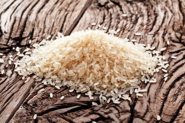 Handful of rice on a wooden table.